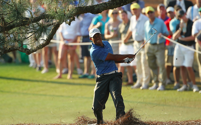 Tiger Woods hits out from the pine straw underneat the Eisenhower Tree at Augusta National. (Getty Images)