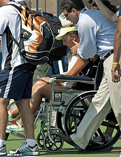 Victoria Azarenka is taken off the court in a wheelchair. (Getty Images)