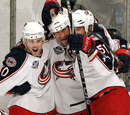 Ethan Moreau (center) celebrates his overtime winner with teammates Kris Russel (10) and Fedor Tyutin. (AP)