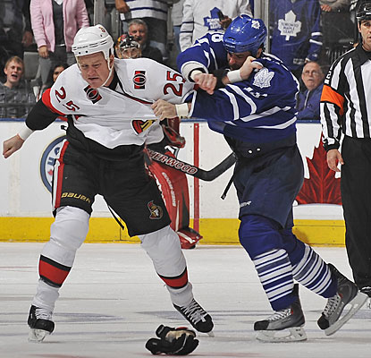 Chris Neil (25) and Mike Brown drop the gloves for the first of three fights in the third period. (Getty Images)