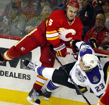 The Kings' Dustin Brown (right) takes a hard hit from the Flames' Mark Giordano during the second period. (AP)