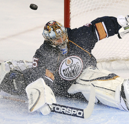 Oilers goalie Nikolai Khabibulin deflects a shot from the Panthers' Chris Higgins during the first period.  (AP)