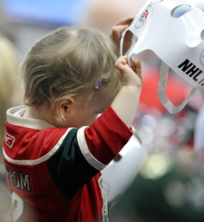 A young Wild fan adjusts a paper helmet prior to the season opener. (Getty Images)