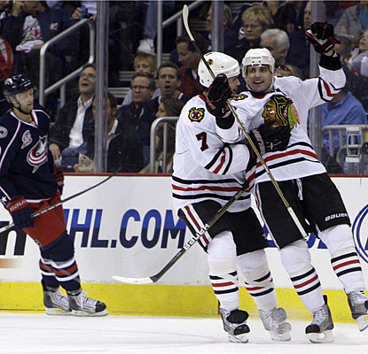 Brent Seabrook chases down Patrick Sharp (right), who scores two goals in a span of 2:02 in the second period. (AP)