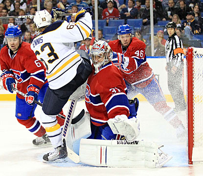 Carey Price combats more than just the puck as center Tyler Ennis is checked into the goalie as well. (US Presswire)