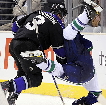 Kings defenseman Jack Johnson upends Canucks left winger Mason Raymond with a big check. (AP)