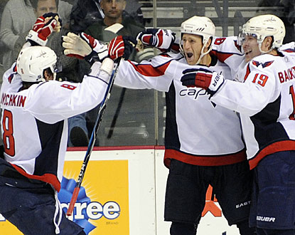 The Caps are happy after Brooks Laich (center) deflects a shot by Alexander Ovechkin (8) in overtime. (AP)