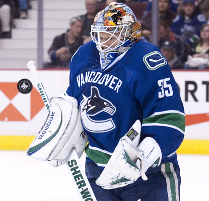 The Canucks' Cory Schneider makes a high save to help hold off the Hurricanes.  (Getty Images)