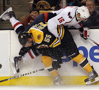 Hard-hitting Johnny Boychuk upends Washington's Eric Fehr with a clean hip check by the boards. (Getty Images)