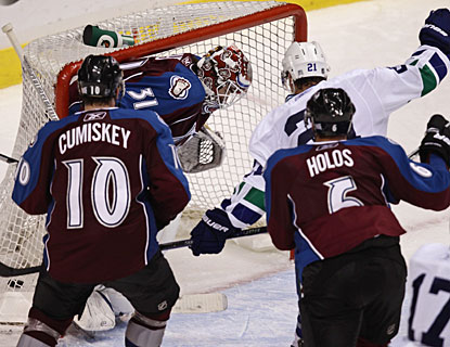 Mason Raymond (21) is fortunate to tap the puck on net and watch it trickle past Peter Budaj. (AP)