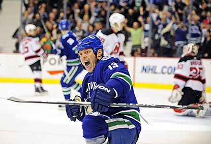 Canucks forward Raffi Torres seems rather pleased after beating Martin Brodeur (right) to open the scoring in the first period. (Getty Images)