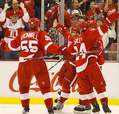 The Red Wings mob Henrik Zetterberg (center) following his game-winning goal 1:23 into overtime.  (US Presswire)