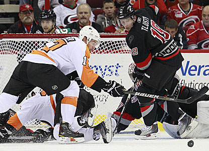 Flyer Jeff Carter fights for the puck in front of Hurricanes goalie Cam Ward before scoring one of his three goals. (AP)
