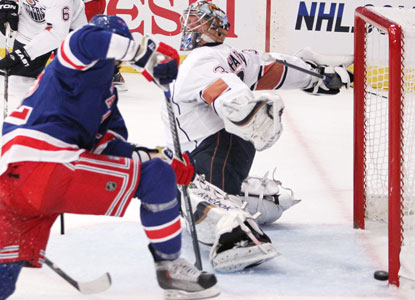 Artem Anisimov, left, scores past Oilers goalie Nikolai Khabibulin for one of the Rangers' four second-period goals. (AP)