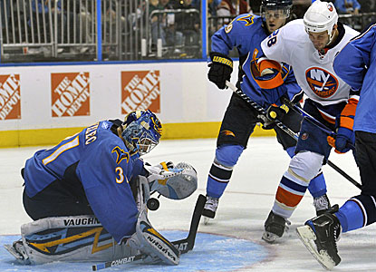 Thrashers goalie Ondrej Pavelec makes a save against Islanders center Zenon Konopka (28) en route to a 28-save win. (AP)