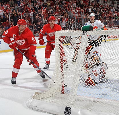 Nicklas Lidstrom gets the puck past a sprawling Miikka Kiprusoff to give the Wings two points.  (Getty Images)