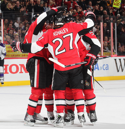 The Senators' Alex Kovalev celebrates with teammates after nabbing his 1,000th career point. (Getty Images)