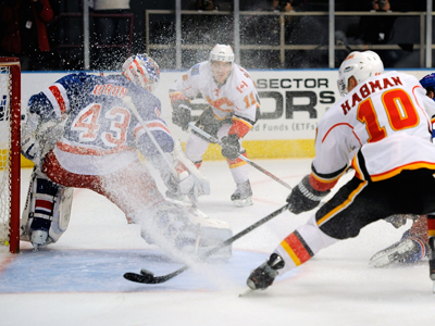 The Rangers' Martin Biron -- 31 saves -- gets iced by the Flames' Niklas Hagman. (Getty Images)