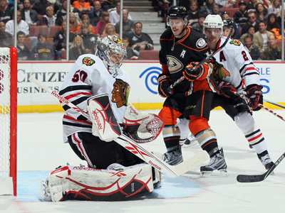 Corey Crawford deflects the puck as the Ducks' Saku Koivu and Duncan Keith battle for position. (Getty Images)