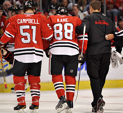 Patrick Kane is helped off the ice after sustaining a left leg injury just 46 seconds into the game. (US Presswire)
