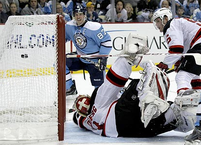 Sidney Crosby (rear) watches as his shot eludes Devils goalie Johan Hedberg and goes into the net.  (AP)