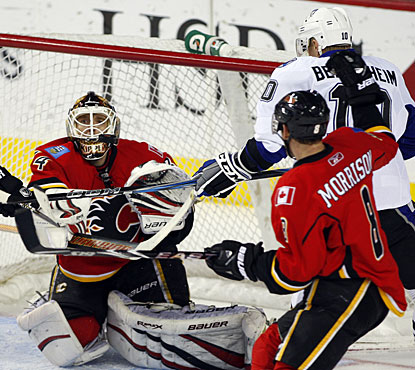 Miikka Kiprusoff finds the puck to grab it while Brendan Morrison defends Sean Bergenheim. (AP)