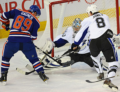 Sam Gagner whacks at the puck, trying to put it past Dan Ellis, but the goalie is able to block the attempt. (AP)
