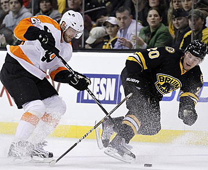 Ville Leino of the Flyers battles Daniel Paille for the puck in overtime before teammate Mike Richards scores the winner. (AP)