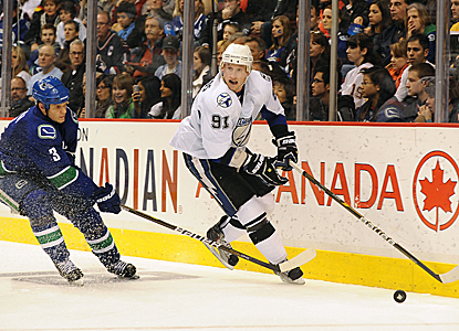 Steven Stamkos is chased down by Vancouver's Kevin Bieska but scores two goals including the overtime winner. (US Presswire)