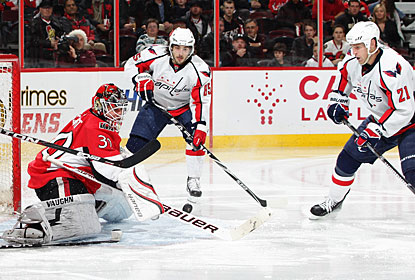 Mathieu Perreault (85), who nets two goals in the contest, and Brooks Laich (21) look for a rebound in front of Brian Elliott. (Getty Images)