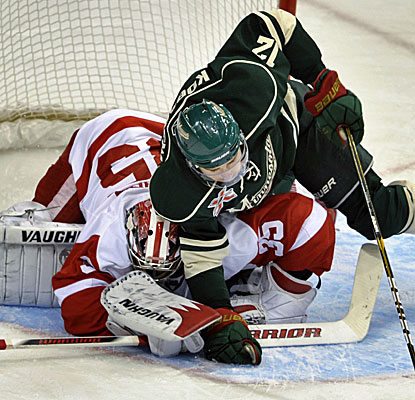 Chuck Kobasew falls over Detroit goalie Jimmy Howard as Howard attempts to cover the puck. (AP)