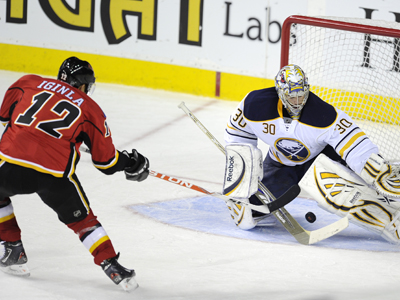 Jarome Iginla puts the puck through the five hole of a flabbergasted Ryan Miller in the second period.  (AP)