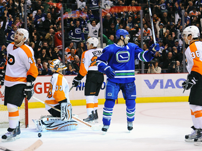 Ryan Kesler celebrates his second of two goals while a dejected Flyers team looks on.  (Getty Images)