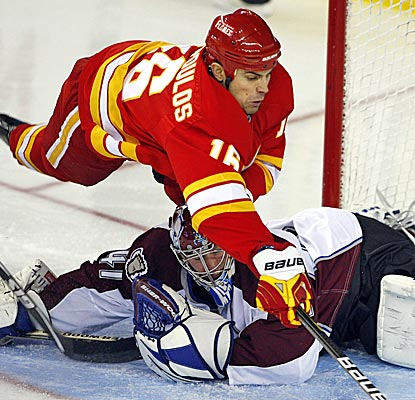The Flames' Tom Kostopoulos dives over Avs goalie Craig Anderson while going after a puck during the third period. (AP)