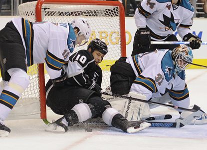 Marco Sturm of the Kings and Dany Heatley of the Sharks take out the net as Sturm tries to score on goalie Antti Niemi. (AP)