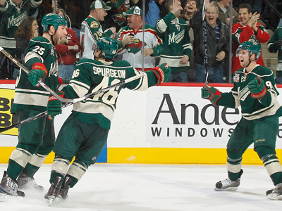 Cam Barker (left) celebrates his OT goal with teammates Jared Spurgeon and Pierre-Marc Bouchard. (Getty Images)
