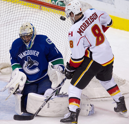 Canucks goalie Roberto Luongo, on his way to 43 saves, deflects the puck wide as Brendan Morrison watches. (AP)