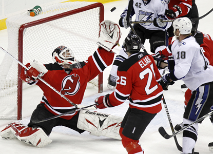 Devils goalie Martin Brodeur reaches up to make one of his 33 saves against the Lightning. (AP)