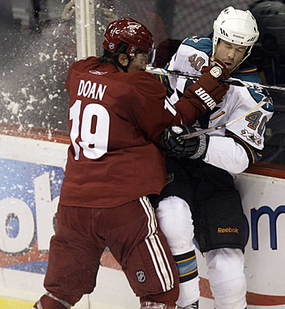 Sharks defenseman Kent Huskins is checked hard into the boards by Coyotes right winger Shane Doan.  (AP)