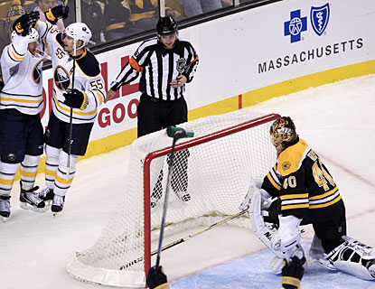Tuukka Rask clears the puck out of his net while Jason Pominville (top left) celebrates his goal for the Sabres. (AP)