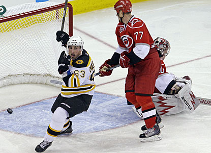 Brad Marchand (63) celebrates Patrice Bergeron's goal while Hurricanes players are helpless in front of the net. (AP)