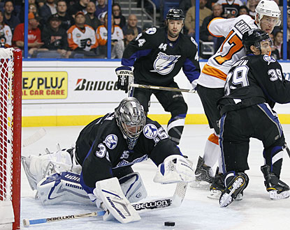 Dwayne Roloson dives over the puck on a rebound to preserve his fourth shutout, all with the Lightning. (AP)