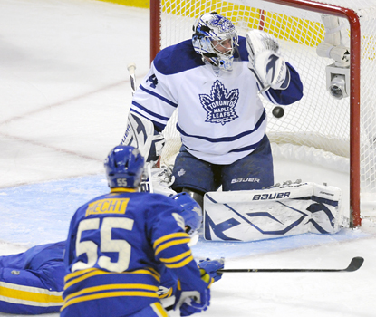 Jason Pominville scores a goal on Maple Leafs goalie James Reimer as teammate Jochen Hecht looks on during the Sabres' win. (AP)