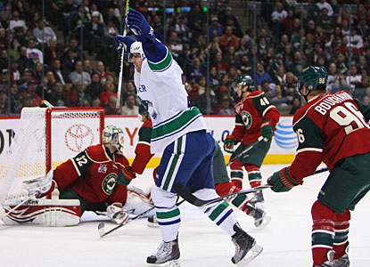 Jannik Hansen gets a backhander by Niklas Backstrom for what eventually proves to be the winning goal for Vancouver. (US Presswire)