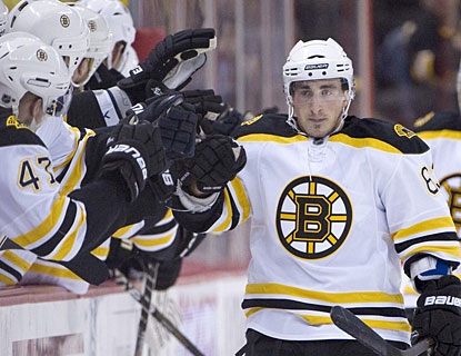 Brad Marchand gets lots of high-fives and appreciation from the bench after scoring his first goal of the night. (AP)