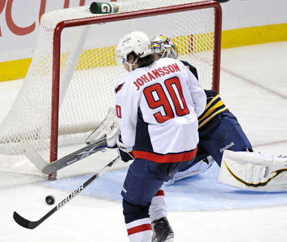 Marcus Johansson deflects a shot from Mathieu Perrault past Sabres goalie Ryan Miller for the game-winning goal. (AP)
