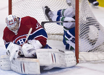 Canucks' Keith Ballard crashes into the net, but Carey Price makes sure the puck does not go in. (AP)