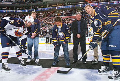 New Sabres owner Terry Pegula watches his son Matthew drop the ceremonial faceoff puck in the game against Atlanta. (Getty Images)
