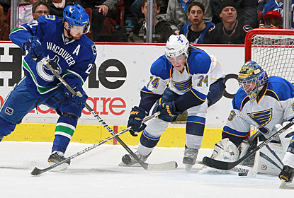 Daniel Sedin makes a move to the net as T.J. Oshie tries to defend and help out goalie Ty Conklin. (Getty Images)
