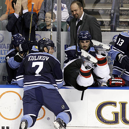 New Jersey's David Clarkson (right) slams and falls into the Panthers' bench during the Devils' 2-1 win. (AP)